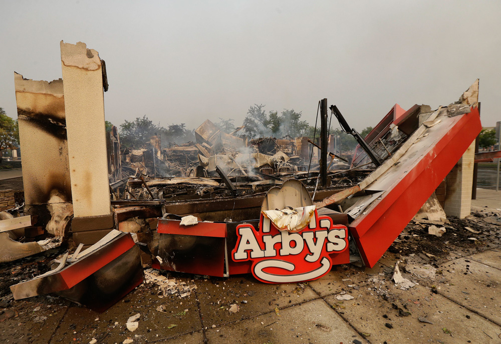 Smoke rises from an Arby's Restaurant that was destroyed by a wildfire in Santa Rosa, Calif., Monday, Oct. 9, 2017. Wildfires whipped by powerful winds swept through Northern California early Monday, sending residents on a headlong flight to safety through smoke and flames as homes burned. (AP Photo/Jeff Chiu)